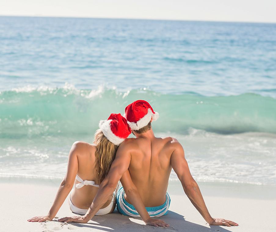 Couple on beach in santa hats