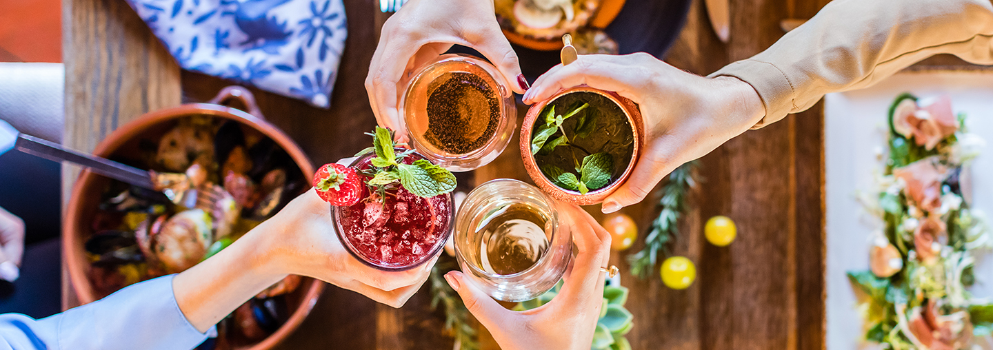Group cheers with cocktails at restaurant