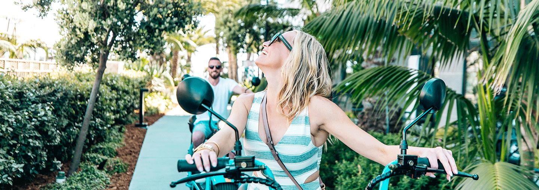 couple riding beach scotters